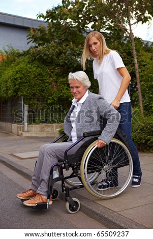 Young woman helping elderly woman in wheelchair over a curbstone - stock photo