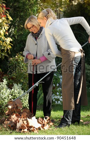 Young woman helping elderly woman to do gardening - stock photo