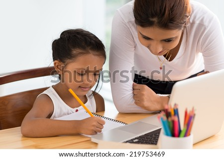 Young woman helping girl with her homework - stock photo