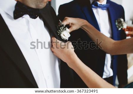 Young woman helping groom in black suit and bow-tie with flower boutonniere before the ceremony - stock photo