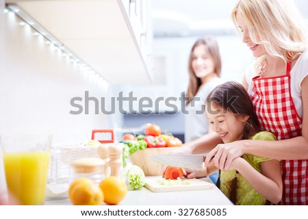 Young woman helping her daughter cut tomato in the kitchen - stock photo