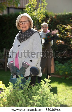 young woman helping senior lady in the garden - stock photo