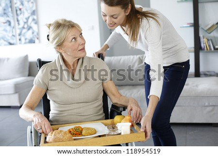 Young woman helping senior woman at home - stock photo