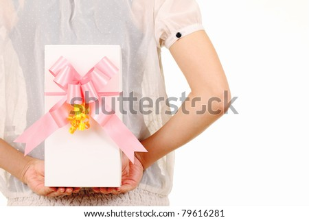 Young woman hide behind back the white gift box