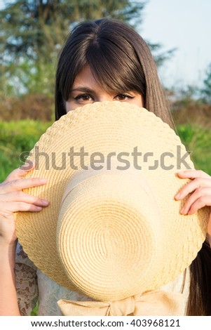 Young woman hiding a face behind a hat - stock photo