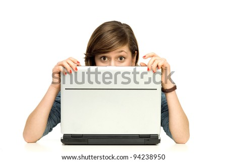 Young woman hiding behind a laptop - stock photo