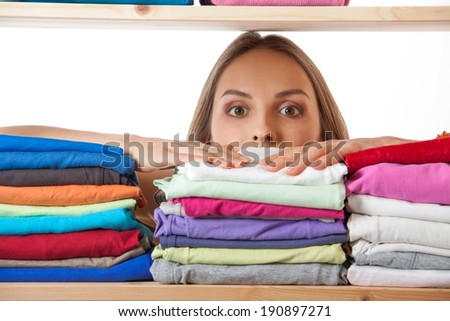 young woman hiding behind a shelf with clothing, isolated on white background - stock photo