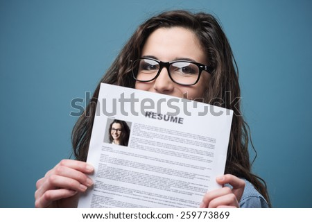Young woman hiding behind her resume - stock photo