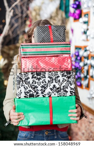 Young woman hiding behind stack of Christmas gifts in store - stock photo