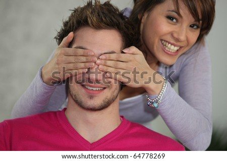 Young woman hiding eyes of a man - stock photo