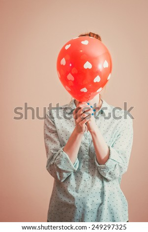 Young woman hiding her face behind a balloon with hearts. Retro colors