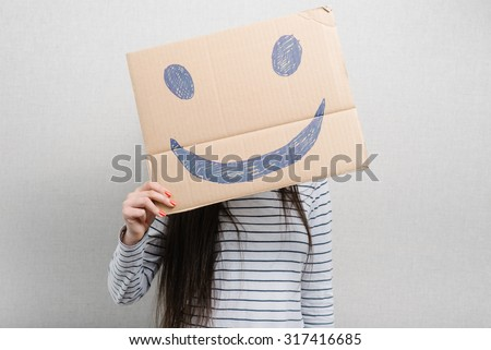Young woman hiding her face with a white paper with a smiley face on it - stock photo