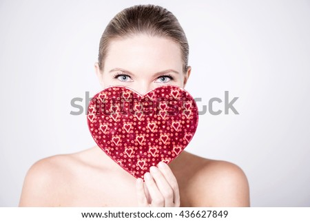 Young woman hiding her face with heart shaped gift box