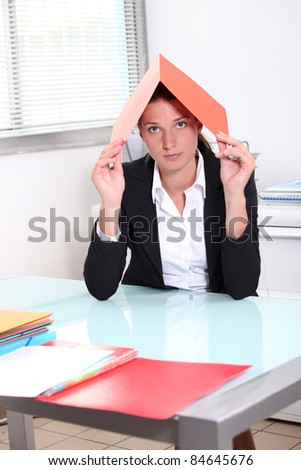 Young woman hiding under a file - stock photo