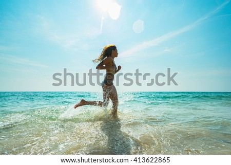 Young woman hight speed running in sea with splashes - stock photo