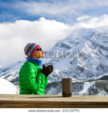 Young woman hiker drink coffee or tea in beautiful Himalaya mountains on hiking trip, Nepal. Active person resting outdoors in winter white nature. Female backpacker camping outside recreation active - stock photo