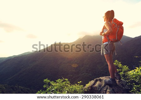 young woman hiker enjoy the beautiful landscape at mountain peak rock - stock photo