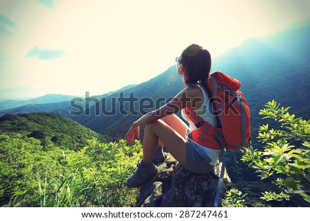 young woman hiker enjoy the view on mountain peak cliff - stock photo