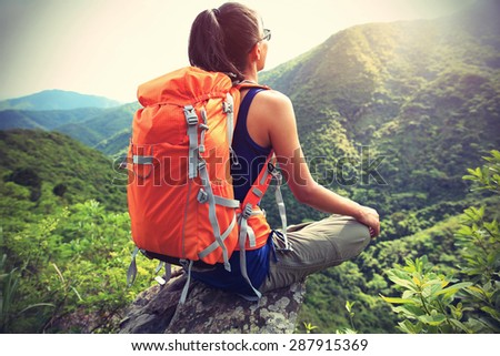 young woman hiker enjoy the view on mountain peak cliff