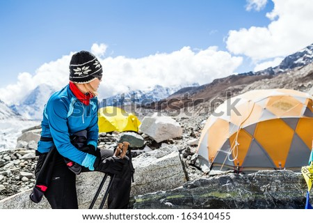 Young woman hiker hiking in Himalaya Mountains in Nepal, Mount Everest Base Camp at 5350m a.s.l on Khumbu glacier camping site - stock photo