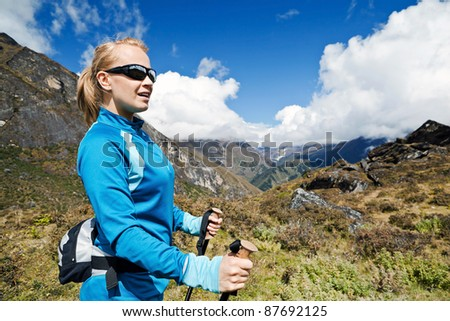 Young woman hiker hiking in Himalaya Mountains in Nepal, nordic walking concept