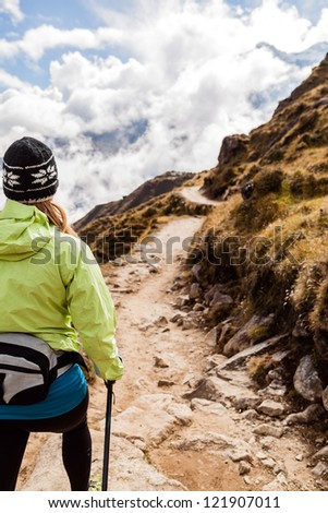 Young woman hiker hiking in Himalaya Mountains in Nepal. Nordic walking, sport and fitness in autumn nature outdoors, beautiful landscape - stock photo