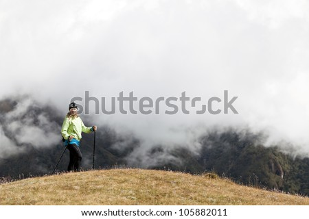 Young woman hiker hiking in Himalaya Mountains in Nepal. Trekking and nordic walking, exercising outdoors. - stock photo
