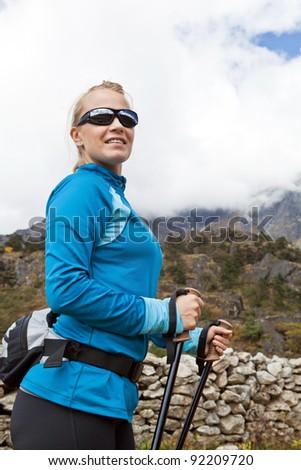 Young woman hiker hiking in Himalaya Mountains in Nepal. Trekking in autumn mountain nature. - stock photo
