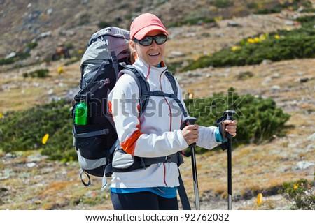 Young woman hiker hiking in mountains, Himalayas Nepal. Walking on trekking trip in autumn Himalaya nature. - stock photo