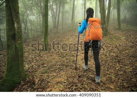 young woman hiker  hiking in spring foggy forest trail