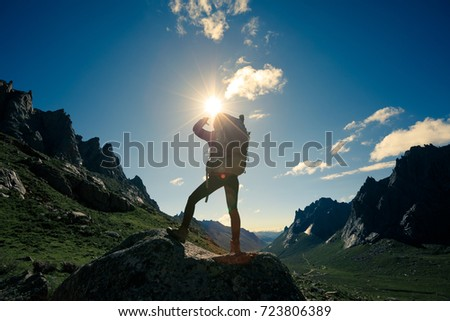 young woman hiker hiking in the sunrise mountain top