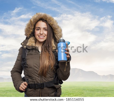 Young woman hiker holding blue water bottle - stock photo