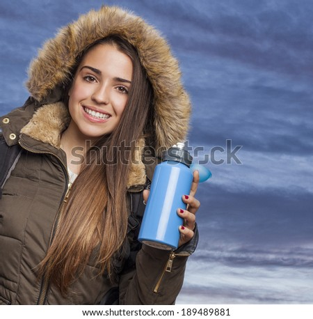 Young woman hiker holding blue water bottle