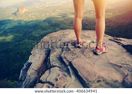 young woman hiker legs on mountain peak rock - stock photo