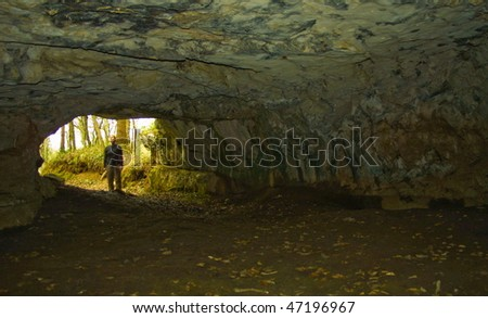 Young woman hiker looking into the cave in dolenjska region in slovenia