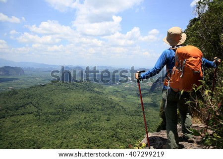 young woman hiker on mountain peak cliff
