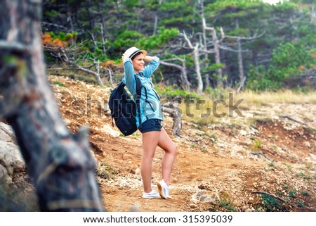 young woman hiker on mountain with backpack, trekking and enjoying fresh air from the forest and nature - stock photo