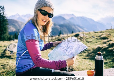 Young woman hiker reading and checking map in mountains on hiking trip. Healthy lifestyle fitness girl camping, drinking coffee and looking at beautiful inspirational landscape view in Tatras, Poland. - stock photo