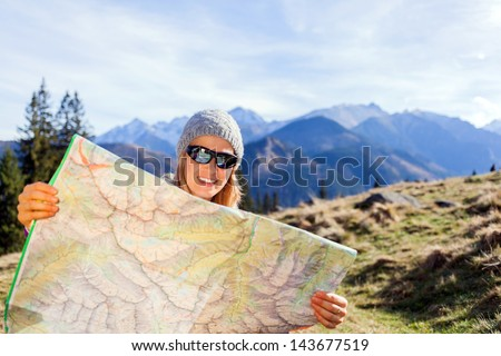 Young woman hiker reading map in mountains on hiking trip. Female trekker camping and planning in autumn nature, outdoors activity and navigation concept - stock photo