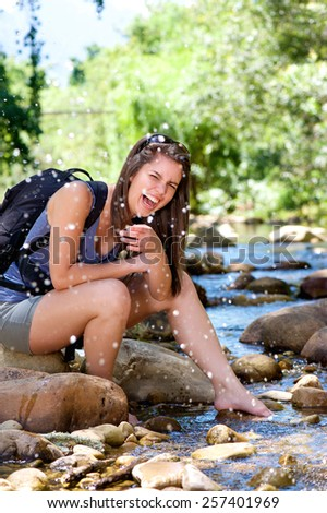 Young woman hiker splashing laughing and water from stream - stock photo