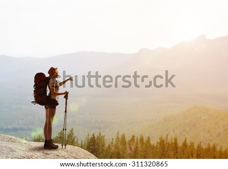 Young woman hiker walking in beautiful mountain nature landscape