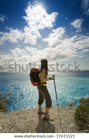 young woman hiking and looking up to the sky - stock photo