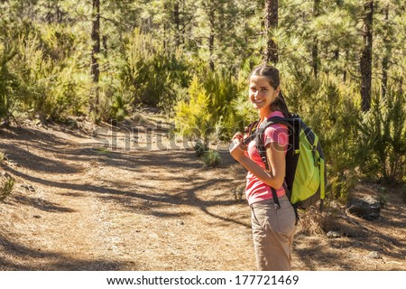 young woman hiking in a pine forest - stock photo