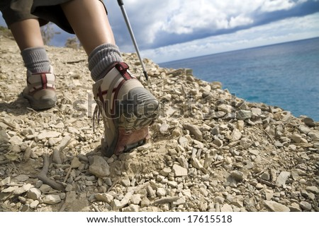 young woman hiking on a cliff near the sea - stock photo