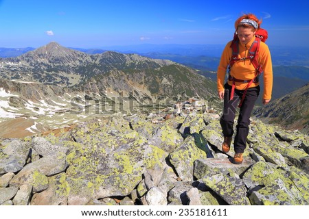 Young woman hiking on the mountain in beautiful spring day - stock photo