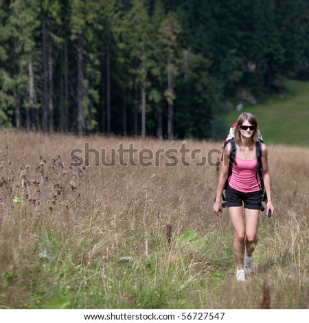 young woman hiking outdoors (going uphill) - stock photo
