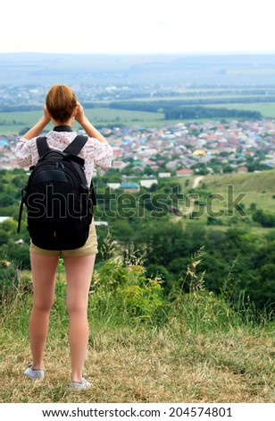 young woman hiking watching through binoculars - stock photo