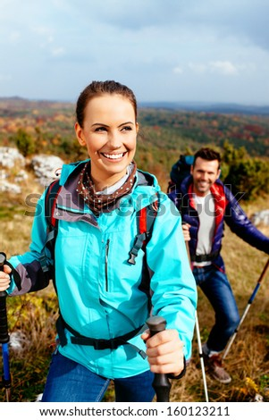 Young woman hiking with friend. Autumn travel. - stock photo