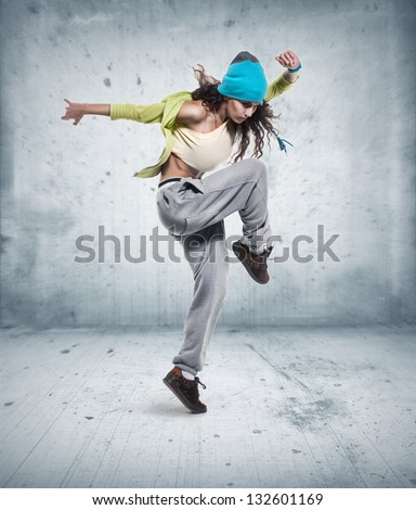 young woman hip hop dancer with grunge wall background texture - stock photo