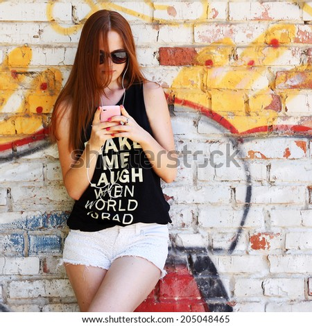 Young woman hipster using a smart phone outdoors near graffiti wall - stock photo